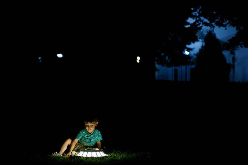 Child is playing with public light in the park. Belgrade, Serbia